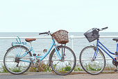 Two bicycles with baskets chained to the fence of promenade in Southwold, UK