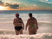 Two big ladies go swimming in the sea at sunset