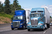 Two big rigs semi trucks in blue tone and different styles and models with semi trailers driving side by side as if competing which one of them stronger on a spacious multi-lane highway