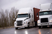 Two of the different make and models big rigs semi trucks with container and dry van semi trailers driving on the raining road to delivery long haul commercial cargo to business partners in evening