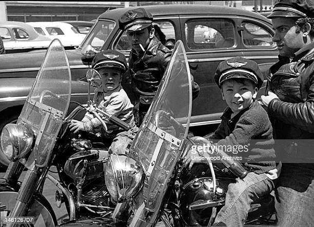 Two bikers wearing caps and leather jackets on their Harley Davidsons with their small sons in front of them San Francisco California mid 1950s The...