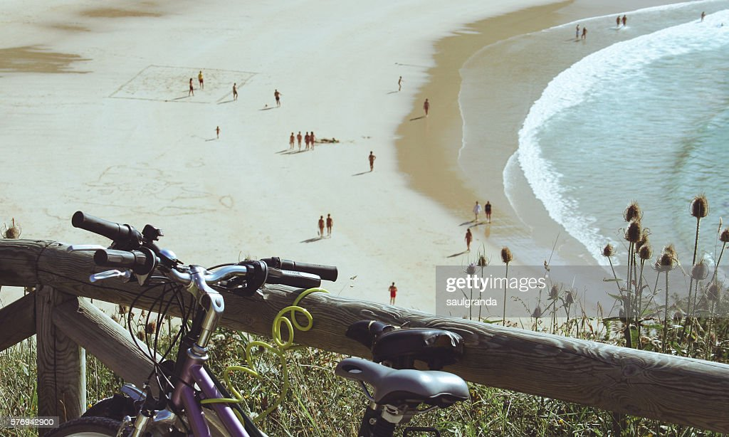Two bikes parking with the nudist beach of Torimbia in the background