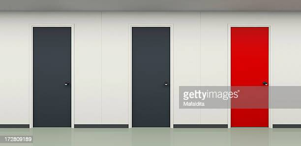 Two black and one red door in office corridor