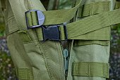 two black plastic snap hook on the harness on the green fabric of the backpack
