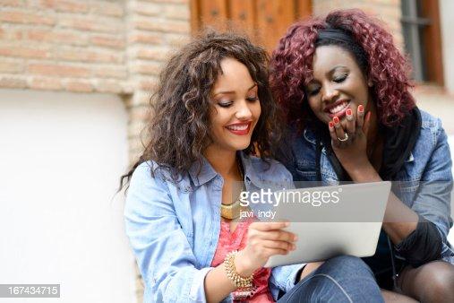 Dois preto Meninas com computador tablet em fundo urbano : Foto de stock