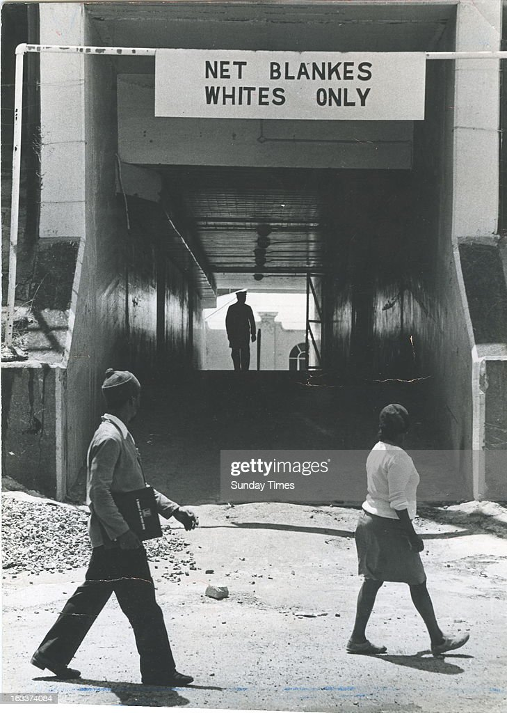 Two black people pass a 'Net Blankes, Whites Only' sign on October 7, 1977 in South Africa.