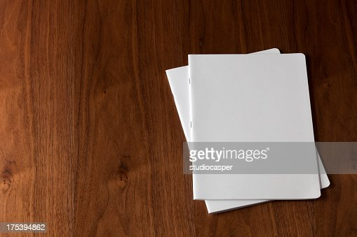 Two blank magazines on a wooden floor