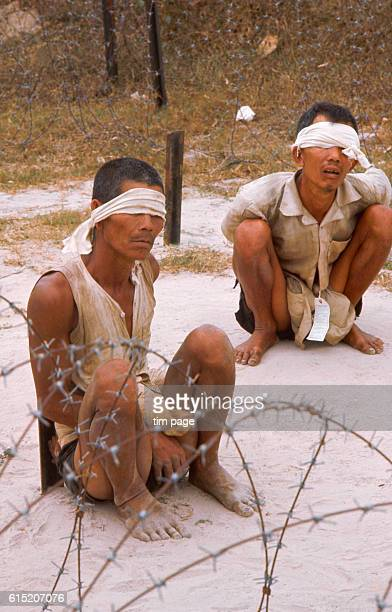 Two blindfolded and bound Vietcong suspects sit inside a barbed wire stockade at the headquarters of the United States Army 25th Division | Location...