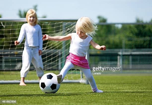 Two blonde sisters playing football