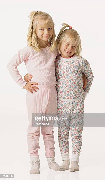 two blonde young sisters stand with arms around each other in their thermals/pajamas