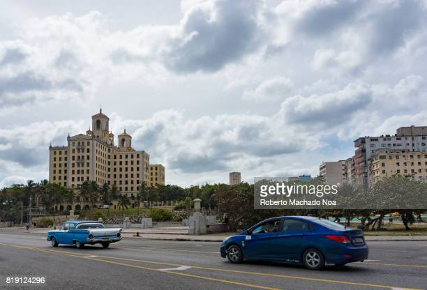 Two blue cars passing by on 'malecon' one is old the other modern With Havana National Hotel in the background