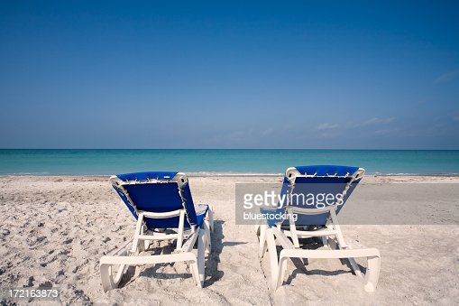Two blue empty beach chairs on white sand facing the ocean