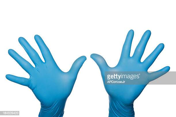 Two blue medical latex gloved hands palms out fingers spread