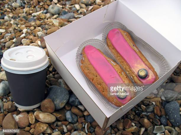 Two blueberry eclairs in a takeout box and a takeawy coffee on the pebbly beach at Brighton, England, United Kingdom