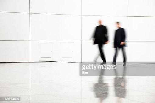Two blurred businessmen walking in hallway