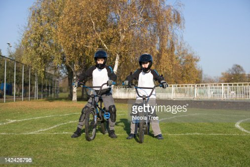 Two BMX riders wearing all the protective gear.