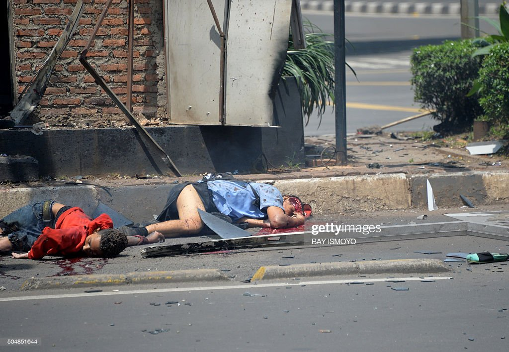 Two bodies lie in the street outside a damaged police post after a series of blasts hit the Indonesia capital Jakarta on January 14 2016 A series of...