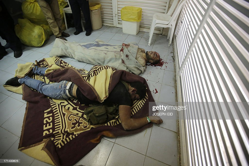 Two bodies lie semi-covered on the floor of a morgue at a hospital in the southern Lebanese city of Sidon, on June 24, 2013. The two men identified as a Palestinian and a Syrian, both Islamist fighters loyal to radical Sunni Muslim Sheikh Ahmad al-Assir, were killed in fighting with Lebanese army troops. At least 12 Lebanese soldiers have been killed in less than 24 hours of clashes with supporters of the radical Sunni cleric in the southern city of Sidon, a military spokesman told AFP.AFP PHOTO/JOSEPH EID