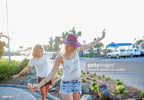 Two Bohemian hipster girls balancing on footpath