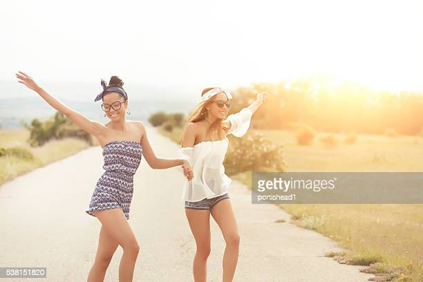 Two boho women holding hands and dancing on the road