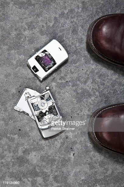 Two booted feet next to a smashed mobile phone