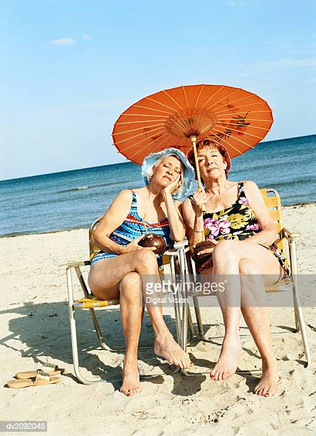 Two Bored Looking Women Sitting on Chairs Under a Parasol