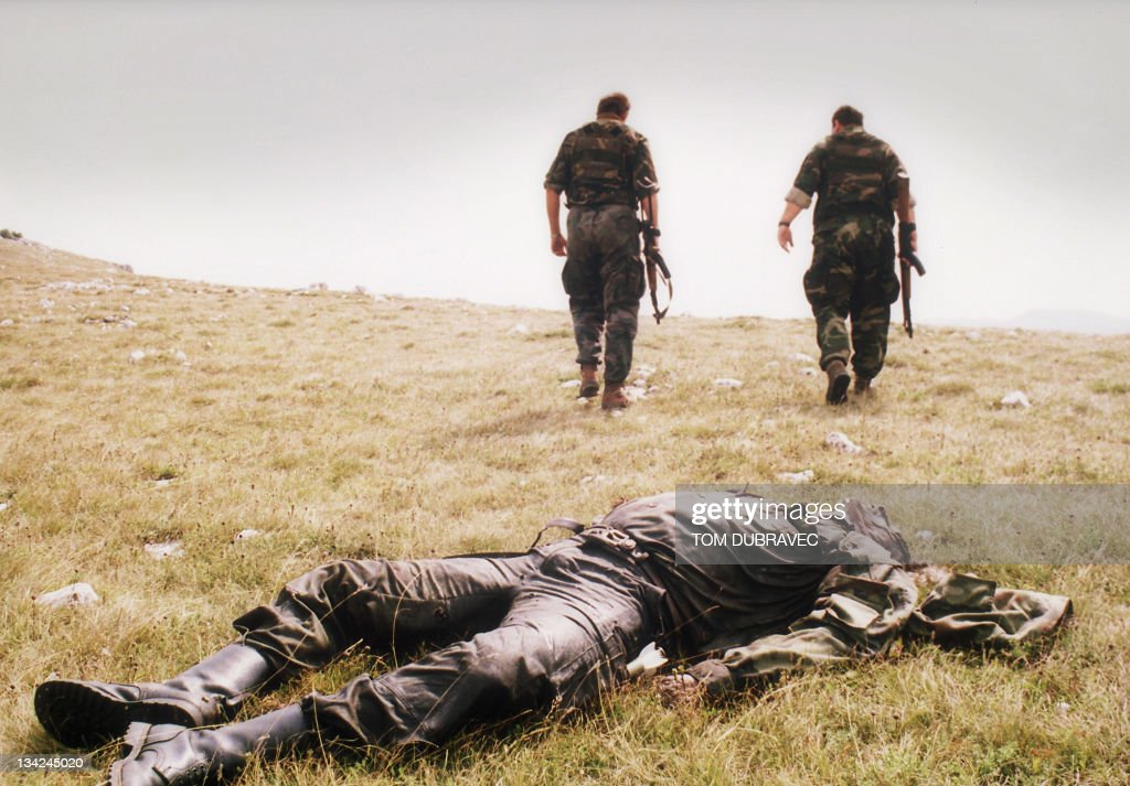 Two Bosnian Croat soldiers pass by the corpse of a Bosnian Serb soldier killed in the Croatian attack on the Serbheld town of Drvar 18 August 1995 in...