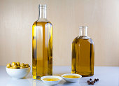 Two bottle olive oil with two test plate, olives bowl and Peppercorns on brown and white