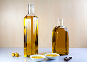 Two bottle olive oil with two test plate, olives and peppercorns on brown and white background