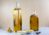 Two bottle olive oil with two test plate, olives, wood spoon and Peppercorns on brown and white
