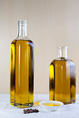 Two bottle olive oil with a test plate and peppercorns on brown and white background