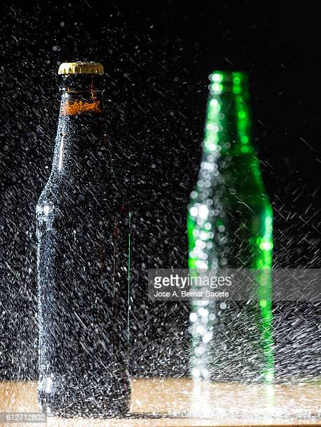 Two bottles of beer of with the crystal misted with water drops on a table of wood