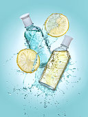 Two bottles of cosmetic  lotion in the big water splash. Two lemon slices near the bottles. Turquoise gradient background