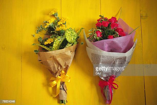 Two bouquets of gerberas and roses, high angle view, yellow background
