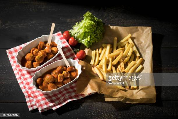 Two bowls of Currywurst and French fries on baking paper
