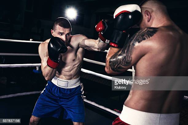Two boxers fighting in a boxing ring