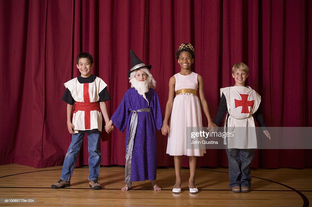 Two boy and girls (8-15) standing on stage, smiling, portrait : Stock Photo