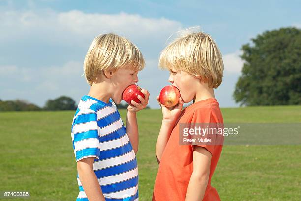 two boy eating apples