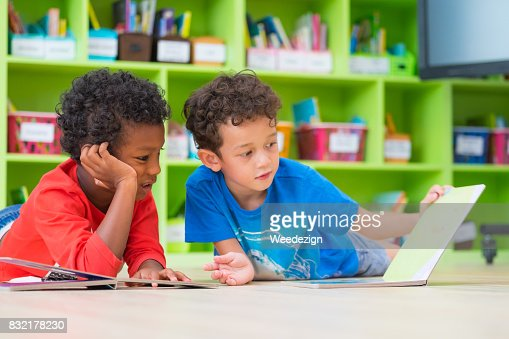 Two boy kid lay down on floor and reading tale book  in preschool library,Kindergarten school education concept : Stock Photo