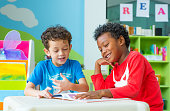 Two boy kid sit on table and reading tale book  in preschool library,Kindergarten school education concept.