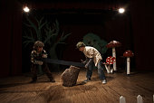 Two boys (9-11) acting as lumberjacks on stage, sawing tree stump