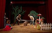 Two boys (9-11) acting as lumberjacks on stage, sawing tree stump