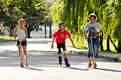 Two boys and girl (9-12)in park,riding scooters and one inline skating