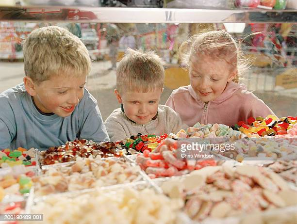 Two boys (4-8) and girl (7-9) looking at sweets in glass counter