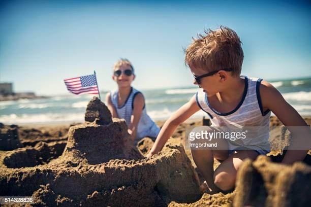 Deux garçons sont la construction d'un château de sable sur la plage