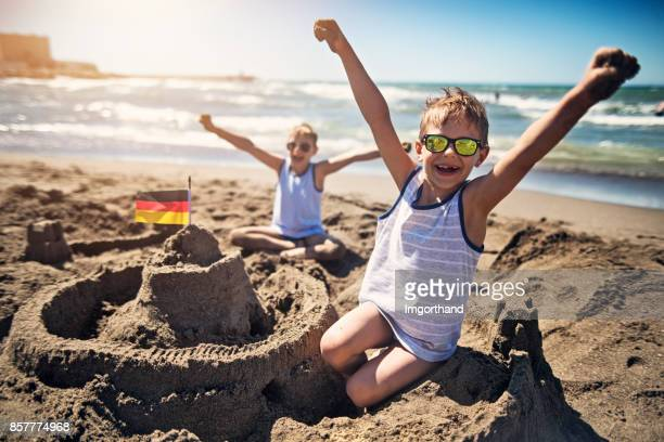 Two boys are building a sandcastle on beach