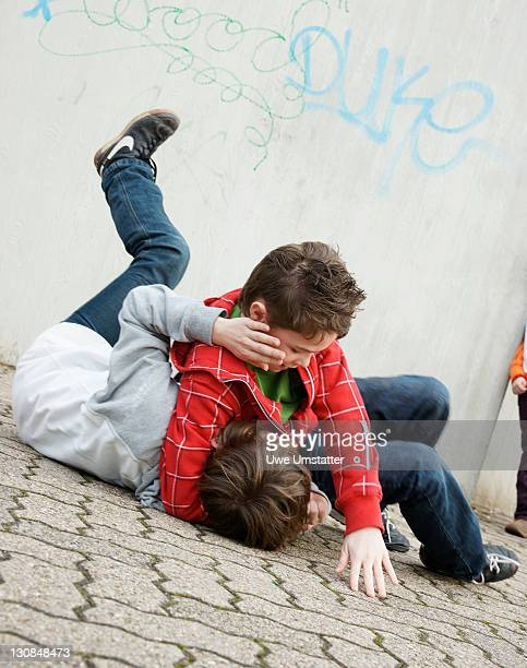 Two boys arguing in the schoolyard, a girl watching