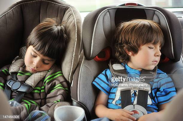 Two boys asleep in their car seats