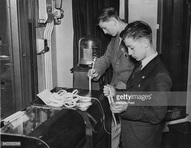 Two boys at a Fleet Street newspaper office in London read the news confirming the DDay invasion on the tickertape machine 6th June 1944 Original...