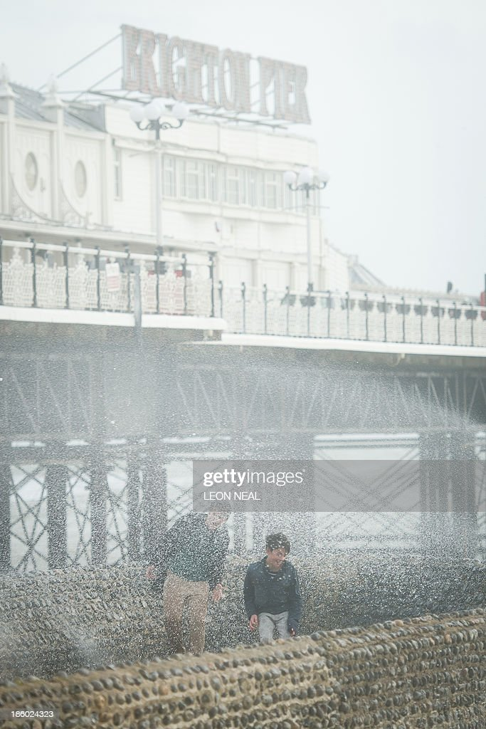 Two boys attempt to evade the spray as large waves crash against the walls of Brighton seafront, in southern England on October 27, 2013 as a predicted storm starts to build. Britain was braced on October 27 for its worst storm in a decade, with heavy rain and winds of more than 80 miles (130 kilometres) an hour set to batter the south of the country. AFP PHOTO / LEON NEAL